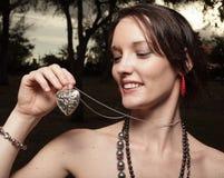 Mujer que sostiene un collar del corazón Imágenes de archivo libres de regalías