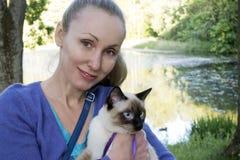 Mujer que sostiene un gato joven en sus brazos en un parque del verano foto de archivo