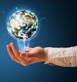 Mujer que sostiene un globo de la tierra que brilla intensamente Imagen de archivo libre de regalías