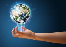 Mujer que sostiene un globo de la tierra que brilla intensamente Imágenes de archivo libres de regalías