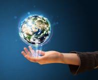 Mujer que sostiene un globo de la tierra que brilla intensamente Foto de archivo