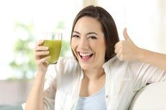 Mujer que sostiene un jugo vegetal con los pulgares para arriba Fotografía de archivo
