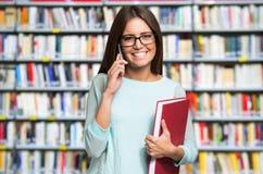 Mujer que sostiene un libro mientras que habla en el teléfono Fotos de archivo
