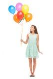 Mujer que sostiene un manojo de globos Foto de archivo libre de regalías