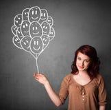 Mujer que sostiene un manojo de globos sonrientes Imagenes de archivo