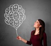 Mujer que sostiene un manojo de globos sonrientes Imagen de archivo libre de regalías