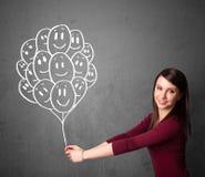 Mujer que sostiene un manojo de globos sonrientes Imágenes de archivo libres de regalías