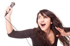Mujer que sostiene un micrófono y que canta ruidosamente Foto de archivo