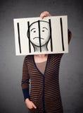 Mujer que sostiene un papel con un preso detrás de las barras en él en f imagen de archivo libre de regalías