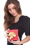 Mujer que sostiene un pequeño rectángulo de regalo rojo Imágenes de archivo libres de regalías