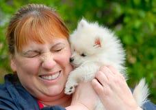 Mujer que sostiene un perrito blanco adorable de Pomeranian Imagenes de archivo