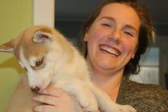 Mujer que sostiene un perrito fornido en la casa imagenes de archivo