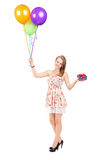 Mujer que sostiene un presente y un manojo de globos Imagen de archivo