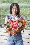 Mujer que sostiene un ramo de flores y de sonrisa Foto de archivo libre de regalías