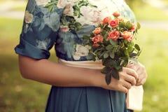 Mujer que sostiene un ramo de verano en el parque, vestido de flores, ingenio Imagen de archivo libre de regalías