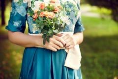 Mujer que sostiene un ramo de verano en el parque, vestido de flores, ingenio Imágenes de archivo libres de regalías