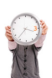Mujer que sostiene un reloj Imagen de archivo libre de regalías