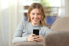 Mujer que sostiene un smartphone que mira la cámara en casa Foto de archivo libre de regalías