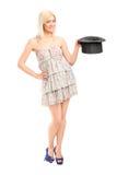 Mujer que sostiene un sombrero del mago Imagenes de archivo