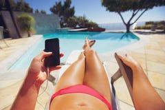 Mujer que sostiene un teléfono elegante por la piscina Fotografía de archivo