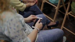 Mujer que sostiene un teléfono en sus manos y que escucha una conferencia almacen de video
