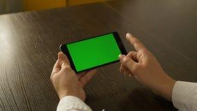 Mujer que sostiene un teléfono móvil con una pantalla verde Para su contenido video almacen de metraje de vídeo