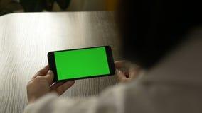 Mujer que sostiene un teléfono móvil con una pantalla verde Para su contenido video almacen de video