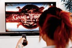 Mujer que sostiene un telecontrol de la TV y mirar el juego de tronos, una creación original de la industria de HBO fotografía de archivo libre de regalías