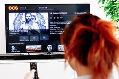 Mujer que sostiene un telecontrol de la TV y mirar las sobras, una creación original de la industria de HBO E imagen de archivo
