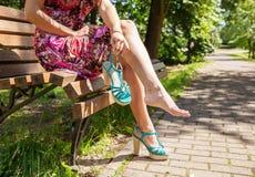 Mujer que sostiene un zapato que se sienta en un banco de parque Imagen de archivo libre de regalías