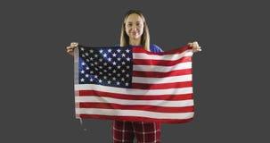 Mujer que sostiene una bandera americana con el polo, barras y estrellas en fondo gris metrajes