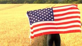 Mujer que sostiene una bandera americana de las barras y estrellas de los E.E.U.U. en un campo de trigo en la puesta del sol o la almacen de video