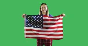 Mujer que sostiene una bandera americana en la pantalla verde dominante de la croma almacen de video