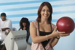 Mujer que sostiene una bola de bolos Imágenes de archivo libres de regalías