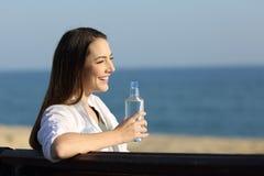 Mujer que sostiene una botella de agua en la playa Fotografía de archivo