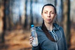 Mujer que sostiene una botella de agua fría en su mano al aire libre, en el parque fotografía de archivo