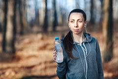 Mujer que sostiene una botella de agua fría en su mano al aire libre, en el parque imagenes de archivo