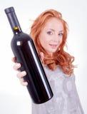 Mujer que sostiene una botella de vino rojo Imágenes de archivo libres de regalías