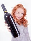 Mujer que sostiene una botella de vino rojo Fotografía de archivo libre de regalías