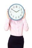 Mujer que sostiene una cara de reloj grande Imagen de archivo