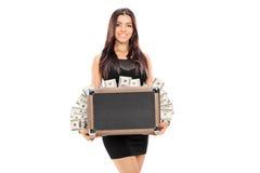 Mujer que sostiene una cartera llena de dinero Foto de archivo libre de regalías