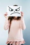 Mujer que sostiene una cartulina con una cara enojada Fotos de archivo