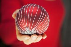 Mujer que sostiene una chuchería de la Navidad Fotos de archivo libres de regalías
