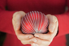 Mujer que sostiene una chuchería de la Navidad Imágenes de archivo libres de regalías