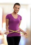 Mujer que sostiene una cinta del meassure alrededor de su cintura Imagenes de archivo