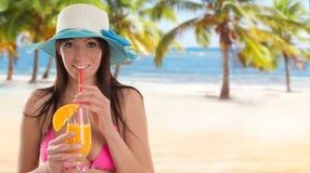 Mujer que sostiene una ensalada de fruta en una playa tropical imagen de archivo