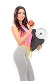 Mujer que sostiene una escala del peso y una manzana Fotos de archivo
