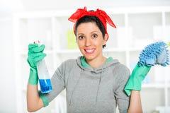 Mujer que sostiene una esponja y un rociador para limpiar Foto de archivo