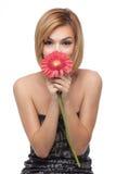 Mujer que sostiene una flor delante de su nariz Fotografía de archivo libre de regalías