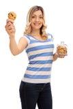 Mujer que sostiene una galleta y un tarro de galletas Foto de archivo